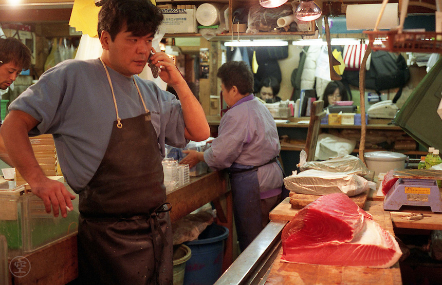A wholesaler talks on his cell phone during the busy morning hours at Tsukiji Fish Market, Tokyo, Japan