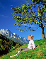 DEU, Deutschland, Bayern, Oberbayern, Berchtesgadener Land:  Frau sitzt unterm Baum in einer Wiese vorm Untersberg | DEU, Germany, Bavaria, Upper Bavaria, Berchtesgadener Land: woman sitting under a tree in a meadow and Untersberg mountain