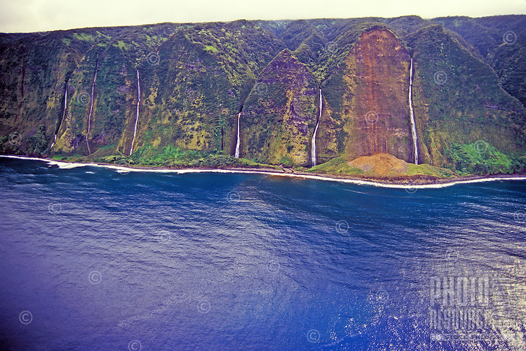 A stunning row of waterfalls pour from the mountains on the beautiful north Kohala coastline.
