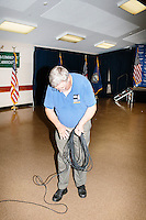Mike Rogers, of the GraniteGrok conservative New Hampshire blog, collects cables after real estate mogul and Republican presidential candidate Donald Trump spoke to supporters at a rally at the Weirs Beach Community Center in Laconia, New Hampshire.