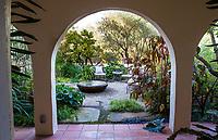 Secret garden Moorish influenced courtyard room seen through arch over tile walkway; McAvoy Garden - California; Design - Ground Studio