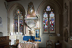 Side chapel altar, stained glass windows inside the church at Urchfont, Wiltshire, England, UK