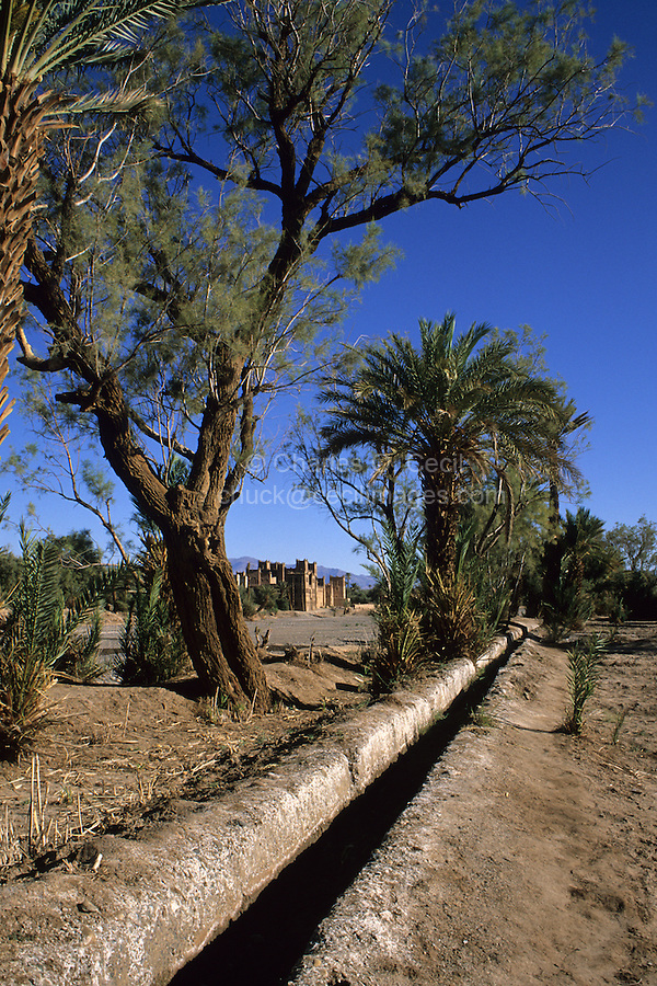 Near Skoura, Morocco - Irrigation Channel Parallel to Dry River Bed; Kasbah Ameridhil in Background.  This area has had greatly reduced rainfall during the preceding eight years.