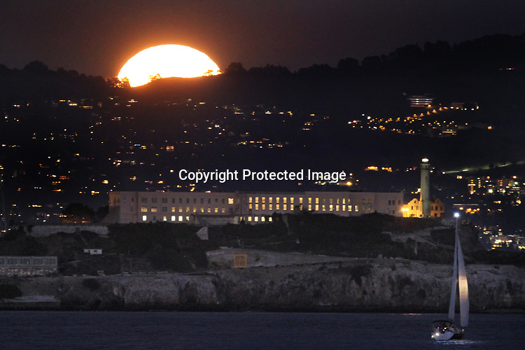 December's full moon rose over the Bay Area hills with Alcatraz Island in the foreground.