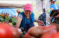 NWA Democrat-Gazette/CHARLIE KAIJO Khou Her of Bentonville arranges produce at her booth during the farmer's market, Saturday, July 7, 2018 at the Square in Bentonville. <br />
