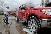 NWA Media/FLIP PUTTHOFF <br /> WASH AND RINSE<br /> Lorraine Wilson washes the family pickup truck on Friday Dec. 26 2014 in Bella Vista. She and her husband, Dennis Wilson, washed the vehicle at their home in the Highlands area of Bella Vista. Rain was in the forecast Friday afternoon, but the Wilsons said they would put the truck in the garage if showers began.