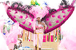 A woman in pink with huge wings waits for the street parade to start during the ZomerCarnaval (Summer Carnival) in Rotterdam, the Netherlands. The street parade is the colorful high point of the Rotterdam carnival. It is a tropical themed parade with over 2000 participants and travels 6km through the center of Rotterdam.