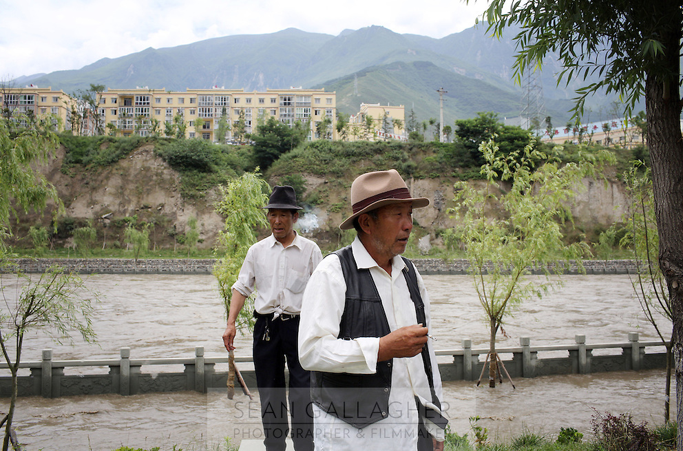 Two Tibetan men walking in front of a river that has breached its banks and flooded a nearby path. Flooding ravaged the region in 2012, causing the displacement of thousands of people. South-east Tibetan Plateau, in Sichuan Province, western China.