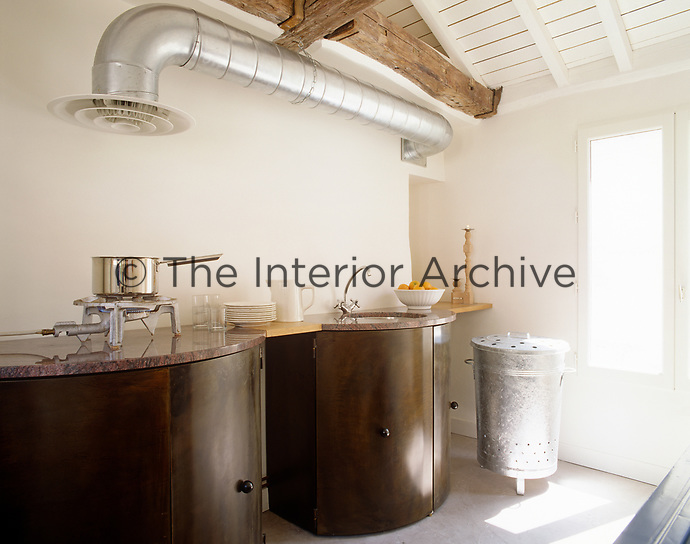 In the kitchen an industrial feel comes from the exposed stainless-steel extractor pipe and large single gas burner