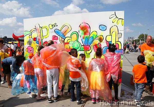 Nederland Amsterdam  2015 06 10 . Landelijke Buitenspeeldag. Honderden kinderen spelen buiten op het NDSM terrein. Kinderen in plastic regencapes spuiten graffiti