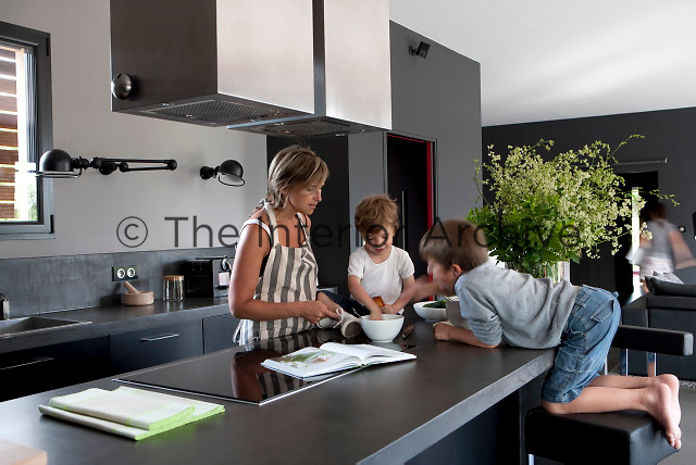 Architect Delphine Bouchet and her two boys discuss the menu in the contemporary kitchen