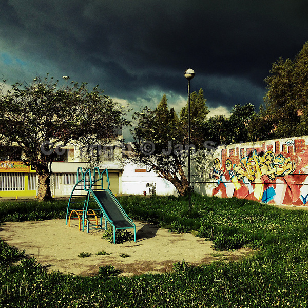 A children's slide is seen at the playground while a usual afternoon storm approaches in Quito, Ecuador, 16 November 2014.