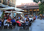 People sitting at street cafe nearby Mercado de San Miguel market, Madrid city centre, Spain