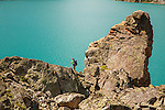 a hiker reaches the prominent rocks near the shore of black canyon lake in beartooth wilderness of montana