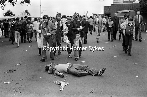 Scottish football fan 'dead drunk', other Scottish fans leave Wembley Football Stadium at the end of the match. 1980s Britain...