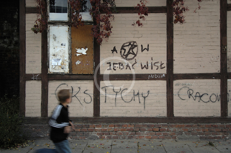 Poland, Krakow, Graffiti on wall, with boy walking past Kazimierz