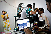 A young woman is amused by an official assisting her husband during the iris scan process as part of the enrollment that is on its way in Naagaaram village, outskirts of Hyderabad in Andhra Pradesh, India. India is assigning each one of its 1.2 billion people a unique ID number based on digital finger prints and iris scan. Photograph: Sanjit Das/Panos