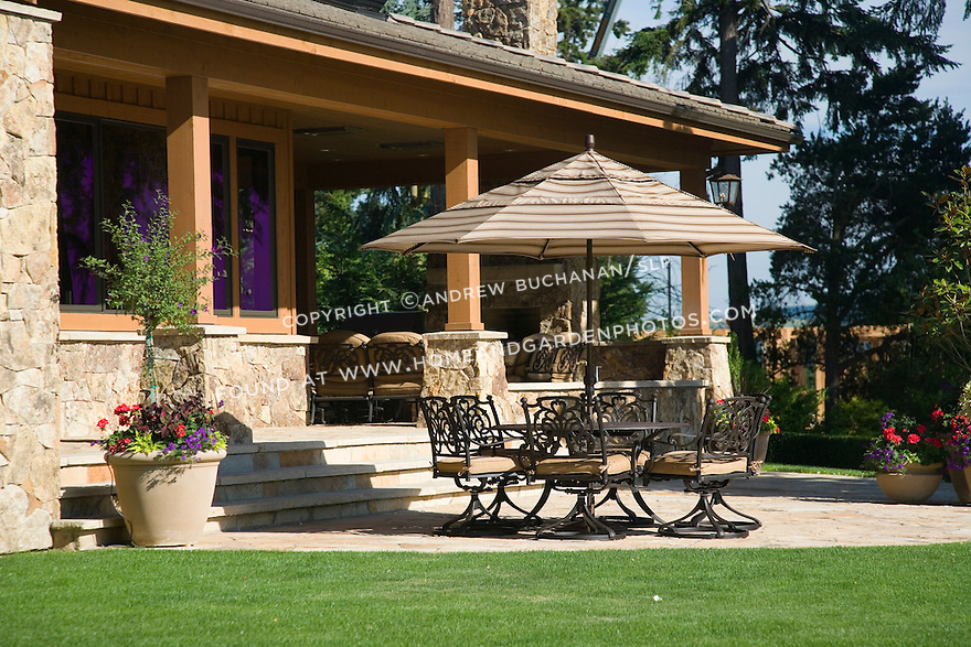 close-up of an open patio with an umbrella covering a dining table and six outdoor chairs in front of a large, lodge like estate sized home under a summer blue sky with a lawn of perfectly manicured green grass and colorful summer pots on the patio