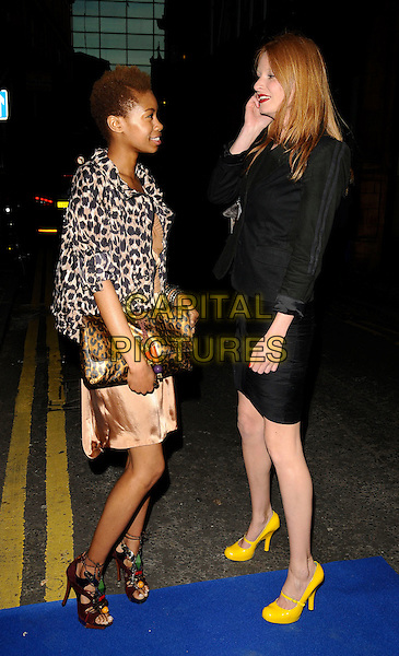 TOLULA ADEYEMI & OLIVIA INGE.The I.N.C. Space launch party, I.N.C. Space, Grape St., London, England..April 29th, 2009 .full length black jacket skirt yellow mary janes shoes beads beaded brown open toe sandals profile leopard print jacket clutch bag silk satin INC.CAP/CAN.©Can Nguyen/Capital Pictures.