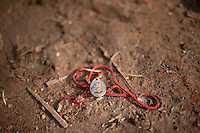 A locket with Buddha's icon lays on the ground. Shanku, near Kathmandu, Nepal. May 9, 2015