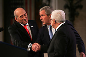 President George W. Bush looks on as Israeli Prime Minister Ehud Olmert on his right and Palestinian Authority President Mahmoud Abbas on his  left., shake hands  during the opening session Middle East Peace Conference  at the U. S Naval Academy in Annapolis, Maryland on November 27, 2007 .  Agency pool photo by Dennis Brack/Black Star