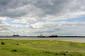 A merchant ship in the Thames estuary close to Tilbury Power Station.