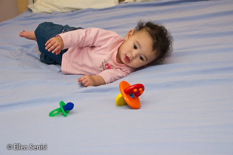 MR / Schenectady, NY. Portrait of infant (girl, 5 months, African American & Caucasian) exhibiting 5-month-old human development milestone behavior as she rolls over. MR: Dal4. ID: AL-HD. © Ellen B. Senisi