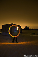 Child twirling light source effect in front of ice fishing hut at night