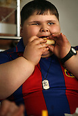 Dzhambulat Khotokhov, 6, one of the fattest boys in the world, eats a hamburger in Nal'chik, near his home town Terek, in southern Russia. .Now 1.4 metres tall and weighing about 100 kg, Khotokhov has grabbed world attention as the biggest kid in the world since he was three. .Khotokhov lives with his mother Neyla and his brother, 14-year-old Mukha. .