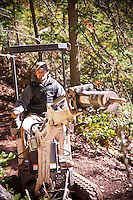Trail builder Aaron Rogers uses a small excavator to build mountain bike trail in Copper Harbor Michigan Michigan's Upper Peninsula.
