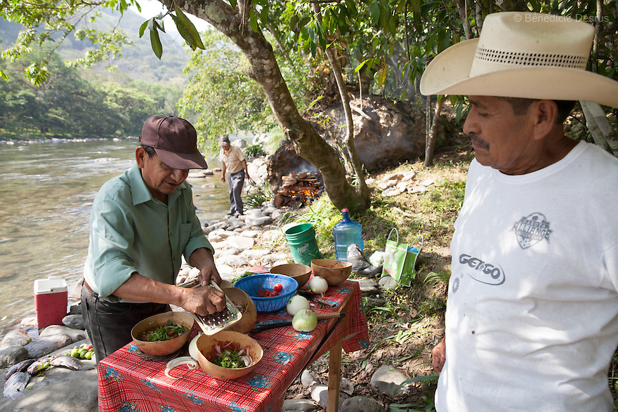 Don Basilio Sabino Hernandez (L) prepares ingredients for caldo de piedra in San Felipe Usila, Mexico on March 30, 2016. Caldo de piedra, or stone soup, is an ancestral dish of the indigenous Chinantec people of San Felipe Usila, a remote village in northern Oaxaca state, Mexico. Traditionally prepared by men in a ritual that dates back to pre-Hispanic times, the soup is cooked in jícara (gourds) by glowing-hot white river rocks that have been heated on a bonfire of orangewood. Ingredients include whole mojarra fish, tomatoes, onion, garlic, chile, epazote, cilantro and fresh water; the soup is seasoned with lime and salt and eaten on the banks of the Usila river. Photo by Bénédicte Desrus