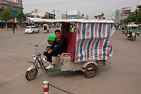 Daytime landscape view of a man in a motorized tricycle taxi Shao Hua Lu in front of the Bozhou Train Station in Bozhou in Qiáochéng Qū in Anhui Province.  © LAN