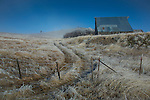 Idaho, North Central, Cottonwood. A road fence and barn in clearing mist on a cold winter morning.