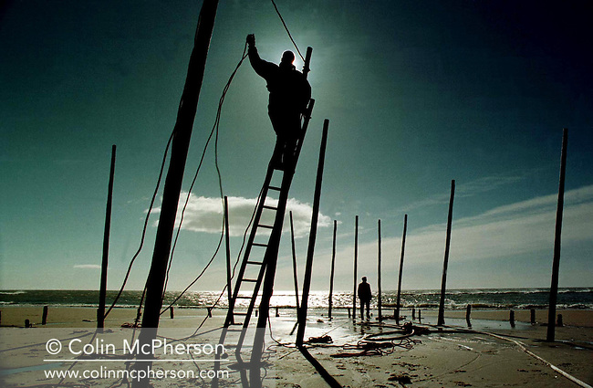 Fishermen at St. Cyrus in Aberdeenshire setting up stake nets on the beach to catch salmon and sea trout between April and August. This age-old practice was abandoned in 1998 due to dwindling fish stocks.