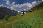Alpine home in spring meadows against the background of the mountains. Hahntennjoch pass. Imst district, Austria.