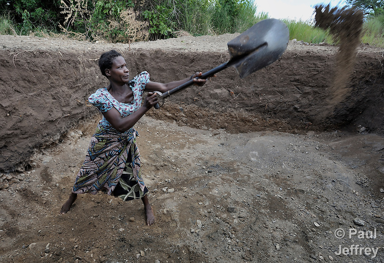 "Agnes Mhona, 27, digs out a reservoir for an irrigation system in Chisatha, a village in southern Malawi on its border with Mozambique. This village has been hard hit by drought in recent years, leading to chronic food insecurity, especially during the ""hunger season,"" when farmers are waiting for the harvest. The ACT Alliance is working with farmers in this village to switch to alternative, drought-resistant crops, such as millet, as well as using irrigation and other improved techniques to increase agricultural yields. Solar panels will power a pump that will draw water from a river into this reservoir and then into six elevated 5,000 liter tanks, which will then provide water to grow crops year round."
