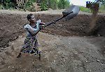 """Agnes Mhona, 27, digs out a reservoir for an irrigation system in Chisatha, a village in southern Malawi on its border with Mozambique. This village has been hard hit by drought in recent years, leading to chronic food insecurity, especially during the """"hunger season,"""" when farmers are waiting for the harvest. The ACT Alliance is working with farmers in this village to switch to alternative, drought-resistant crops, such as millet, as well as using irrigation and other improved techniques to increase agricultural yields. Solar panels will power a pump that will draw water from a river into this reservoir and then into six elevated 5,000 liter tanks, which will then provide water to grow crops year round."""