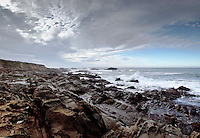Clouds and blue sky over the craggy coast at Bean Hollow State Beach, California.  This panoramic view was created using three images stiched together in Photoshop.