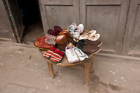 Daytime landscape view of a table with shoes at the entrance to a traditional siheyuan in a hútòng in Lizhuang old town in the Yíbīn county Cuiping District in Sichuan Province.  © LAN