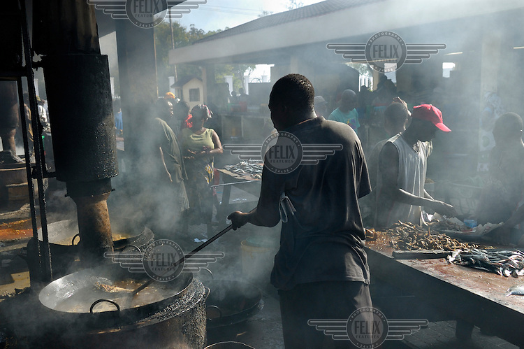 Frying fresh fish at Magogoni fish market.