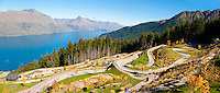 Panoramic Photo of the Luge above Queenstown, South Island, New Zealand. From the centre of Queenstown, after catching a gondola ride into the mountains above Queenstown, you are presented with a whole host of adventure activities including luging (seen in the photo), a bungee jump and the skywing. Not only is it great fun, but its is in the most incredible location with uninterrupted panoramic views over the entirity of Queenstown and Lake Wakatipu, with the Remarkables Mountain Range providing the perfect backdrop.
