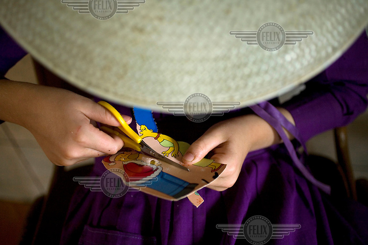 A child cuts out Simpsons characters from a cereal box. She hasn't seen The Simpsons on television as Mennonites don't agree with technology so don't own televisions. Near the city of Santa Cruz, there are about 15,000 Mennonites living in isolated communities. Mennonites are a group of Christian Anabaptists, part of the peace churches who are committed to non-violence, non-resistance and pacifism and place a strong theological emphasis on voluntary service.