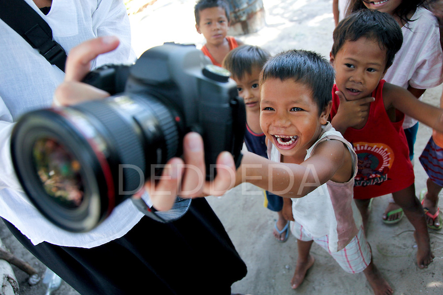 Deddeda shows children photos that she took of them, on her camera, in Corong Corong, Palawan, Philippines.