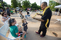 Jonny Galvis (from right) of Bella Vista shows his reticulating python Friday, June 19, 2020, to Margo Ballay, 3, Joseph Lyon, 8, and their mom Elizabeth Lyon-Ballay of Bella Vista during a Juneteenth cookout at Lawrence Plaza in Bentonville. Go to nwaonline.com/200620Daily/ to see more photos.<br /> (NWA Democrat-Gazette/Ben Goff)