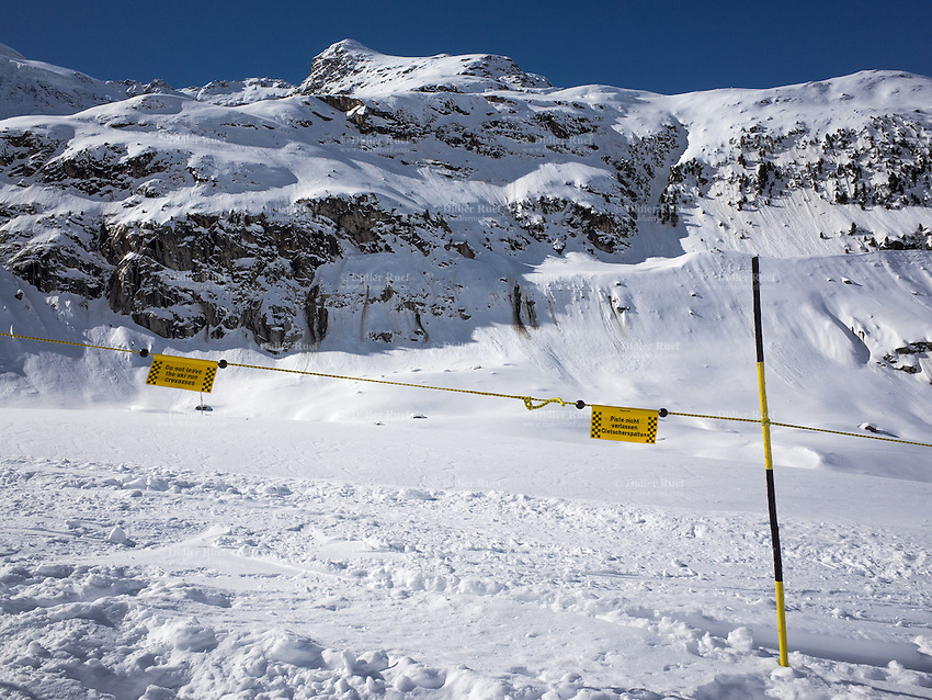 Switzerland. Canton Graubunden. Upper Engadin. Diavolezza. Especially popular is the difficult 10 km slope down the Morteratsch Glacier to the Morteratsch railway station. The slope on the glacier is marked and secured in order to avoid accidents due to crevasses. Warning signs: Yellow pole, lines and signs written in english and german: Do not leave the skin runs. Crevasses. Ski tourists and skiing fans, alpine fanatics, climbing addicts and hiking aficionados. Alpine panorama. Swiss Alps.  The Diavolezza (in the local variant of Italian, She-Devil) is a mountain in the area of Pontresina in Graubünden. 7.03.2014 © 2014 Didier Ruef