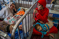 KABUL, AFGHANISTAN - SEPTEMBER 21: (R) Salima, 19, from Logar province, holds her malnourished daughter Samina, 1 1/2 years old, as she and other children receive treatment for malnutrition at the Indira Gandhi Children Hospital on September 21, 2013 in Kabul, Afghanistan.