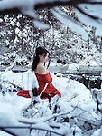 Beautiful woman in red kimono with bare shoulders sitting on snow in a winter nature scenery by a river