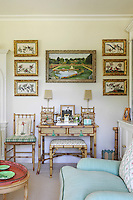 Oriental style bird paintings in gilt bamboo frames hang above a bamboo desk and stool in the sitting room