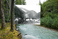 KLGO Photo Station CH-02: Canyon City. August 18, 2013, View to the north of the Taiya River near Canyon City, Klondike Gold Rush National Historical Park, Alaska, United States. The photo was taken by Ronald D. Karpilo Jr. The historic photo taken August 30, 1897 by Frank La Roche (University of Washington Libraries, Special Collections, UW28136) is digitally overlaid on the repeat photo.