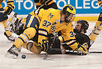 March 26,  2011                     Michigan defenseman Mac Bennett (37) falls atop Colorado center Rylan Schwartz (13) in front of the University of Michigan Wolverines net in the second period. The University of Michigan was leading Colorado College 2-0 after two periods in the championship game of the NCAA Division 1 Men's West Regional Hockey Tournament, on Saturday March 26, 2011 at the Scottrade Center in downtown St. Louis.